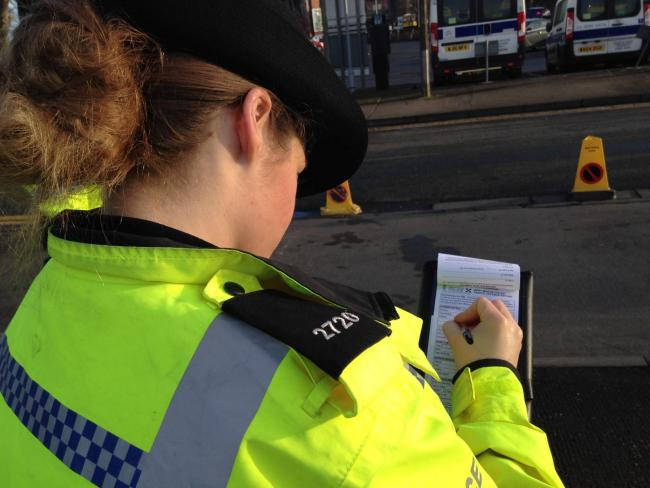 PENALTY: A West Mercia police officer writes out a ticket. Photo by James Connell..