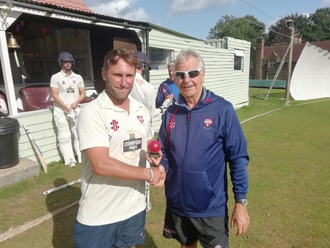 Dan Conway receives a mounted cricket ball to mark his achievement in reaching 100 championship wickets for Herefordshire from chairman of cricket Ian Macklin.