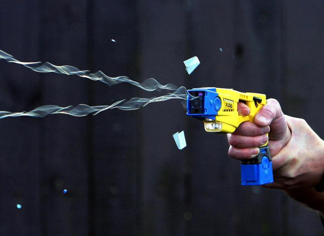 File photo dated 24/11/08 of Taser stun gun demonstration, as a man died after he was shot with a Taser by police responding to reports of a house burglary. PRESS ASSOCIATION Photo. Issue date: Monday December 22, 2014. Staffordshire Police said officers
