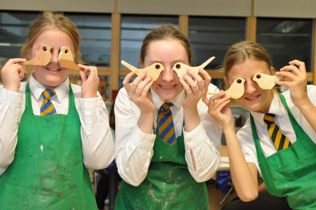 Year 9 students showing off their work in DT making bird-shaped door stops