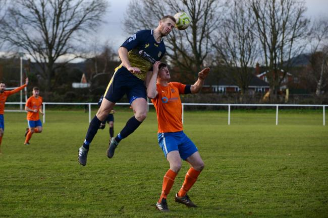 Wellington FC reserves v Holme Lacy FC - Holme Lacy striker Nick Britton rises above Matt Maturi to win a header.