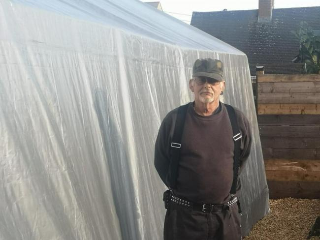 Steve Matthews next to his temporary garage, put up to protect his classic cars