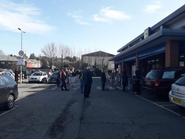 Hereford Times: Shopper queue outside Hereford's Lidl in March 2020