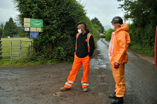 Contractors in PPE, waiting to go onsite, outside Rook Row Farm in Mathon, near Malvern, Herefordshire. Picture: Ben Birchall/PA Wire