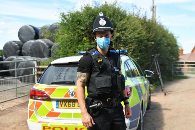 Hereford Times: A police officer wearing a face mask at Rook Row Farm on Sunday. Picture: Jacob King/PA Wire