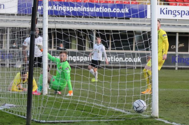 Hereford Times: Lenell John-Lewis squeezes his effort home to fire Hereford level. Picture: Steve Niblett/Hereford FC