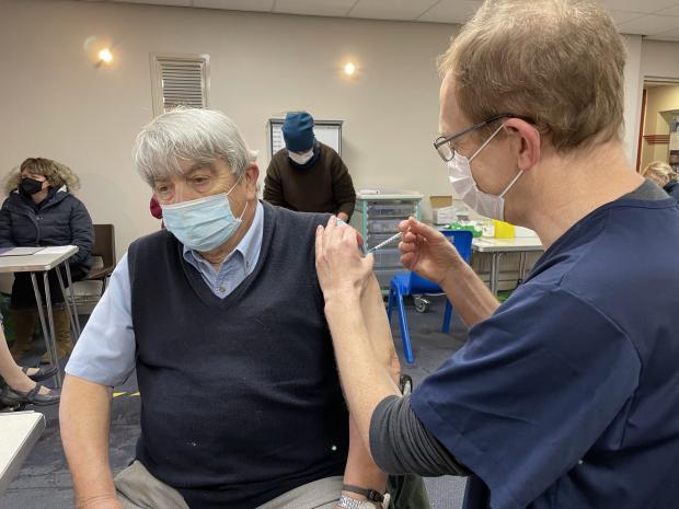 Hereford Times: Dr Simon Lennane, right, gives Bernard Morris his coronavirus jab in Ross-on-Wye's Larruperz Centre