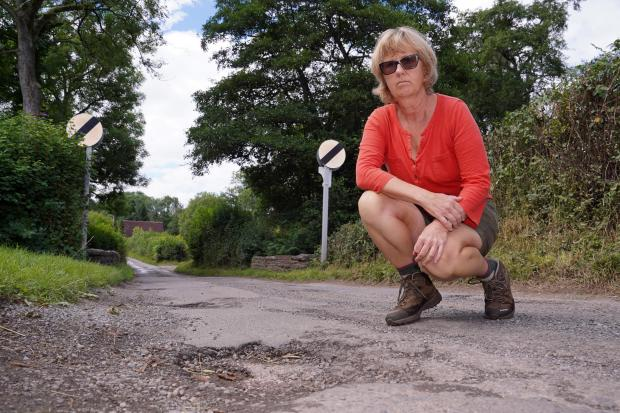 Hereford Times: Sarah Bell shows the potholes along Prill Road in Ewyas Harold, which she says should be a priority. Picture: Rob Davies