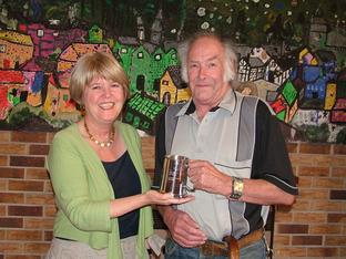Karen Plant, chairman of Knighton Community Centre, presenting Tony Sharp with an engraved tankard.