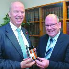 Judge Philip MacKenzie (left) presents the Imperial Service medal to Richard Thomas.