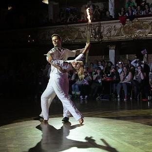 Harry Judd and Aliona Vilani dancing with the Olympic Flame inside Blackpool's Tower Ballroom (LOCOG/PA)