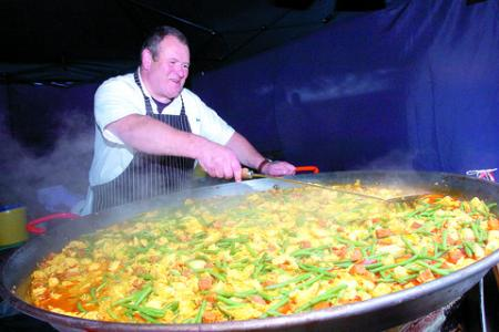 Mark Williams from Key Cottage Catering stirring a giant pan of paella.