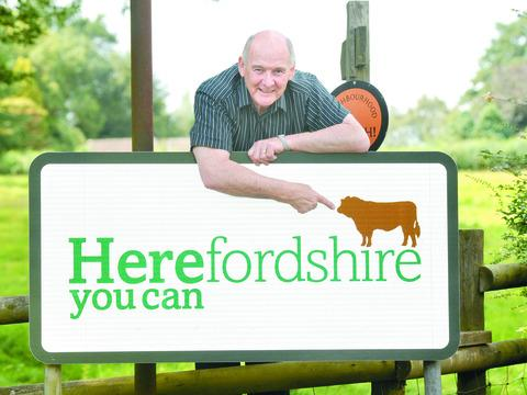 Herefordshire Council leader John Jarvis with a new boundary sign