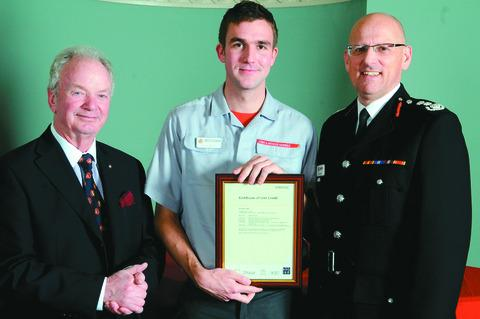 Wayne Hoskins receives his award from fire and rescue authority chairman Councillor Derek Prodger (left) and chief fire officer Mark Yates