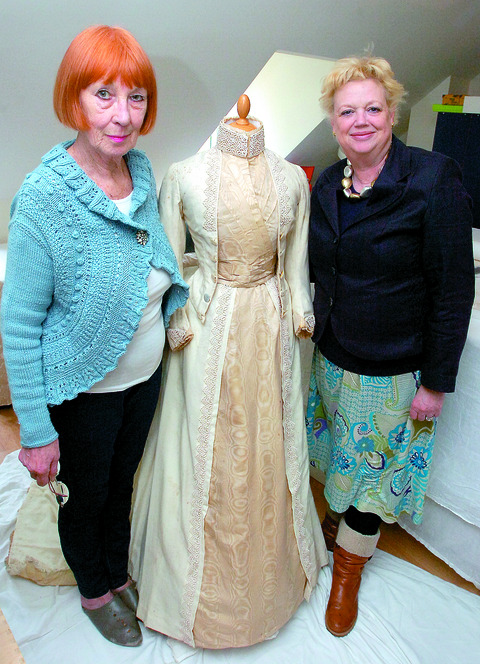 Textile conservator Eve Finney (left) and Alexandra James of Broadfield Court with the dress.