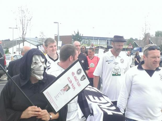 Hereford United fans carry coffin in a funeral procession through city to m