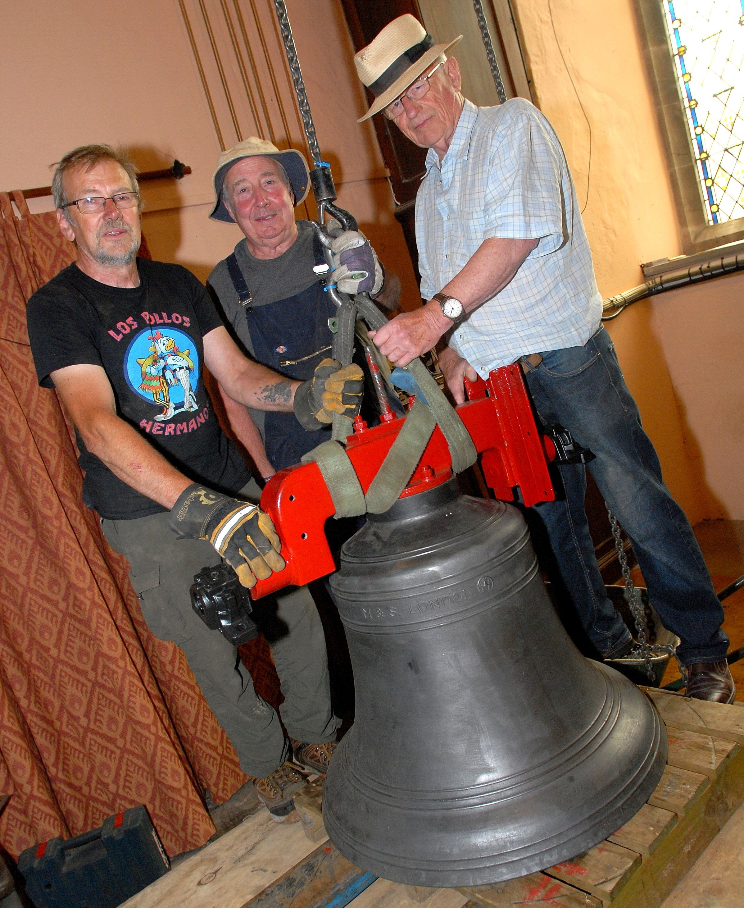 Seen here, from left to right - bell hanger Phil Dunnett with volunteers Paul Grey and Arthur Pearce inspect one of the restored bells bef