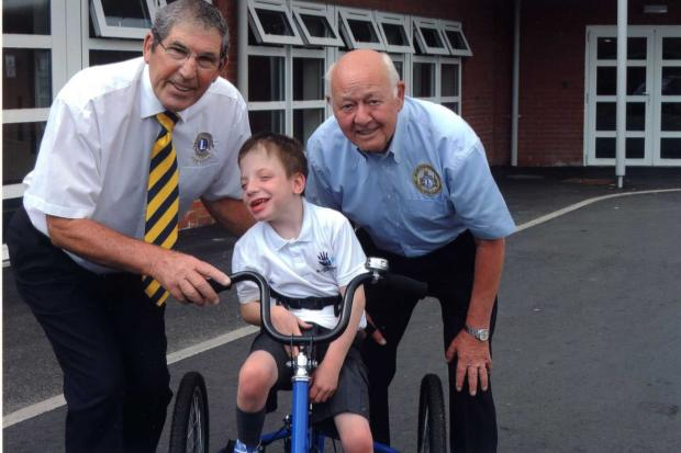 Ben shows off his new trike to Lions Club president David Barrett (right) and fellow Lions Club member, Ron Williams.