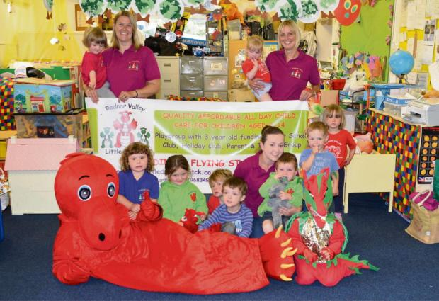 Photo: Staff members Debbie Davies playgroup assistant, Jane Bartlett leader and Stacey Millichamp assistant and children at the playgroup get to meet Dai the dragon who will be special guest at their open day.