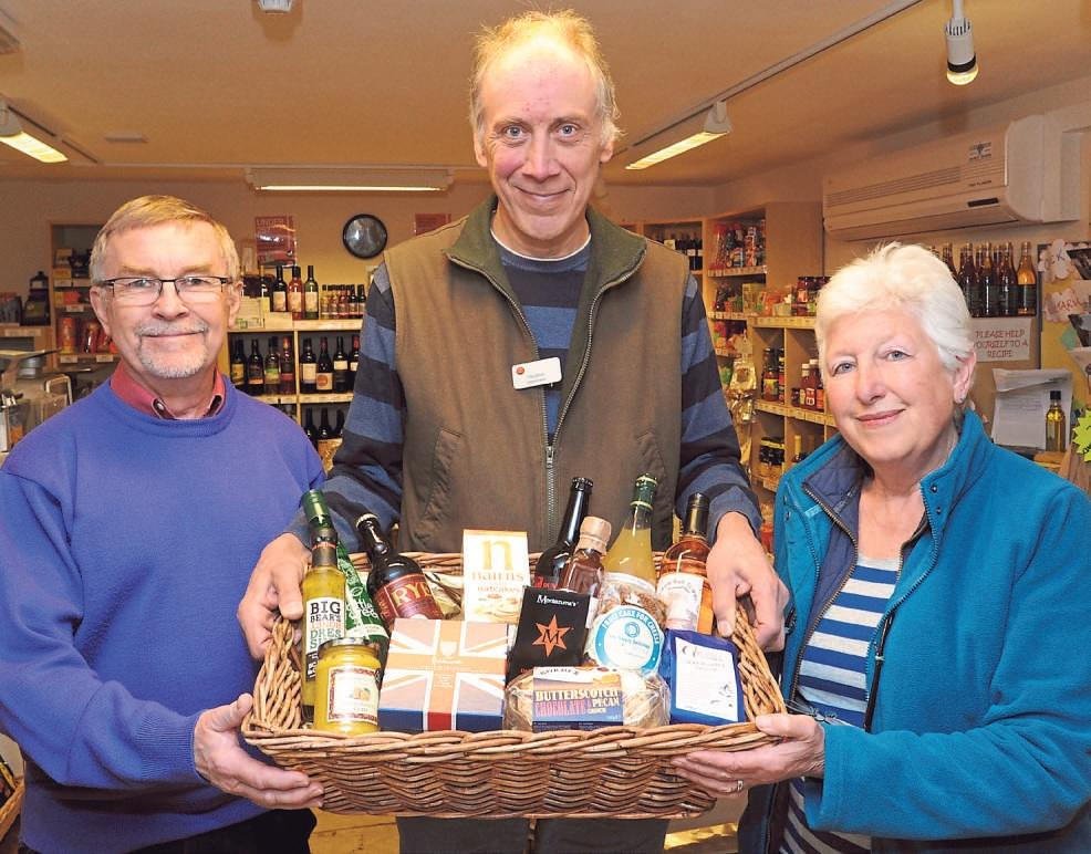 At Yarpole village shop are treasurer David Cheshire (left), subpostmaster Chris Smith and volunteer Felicity Norman with a hamper to be won at the birthday raffle