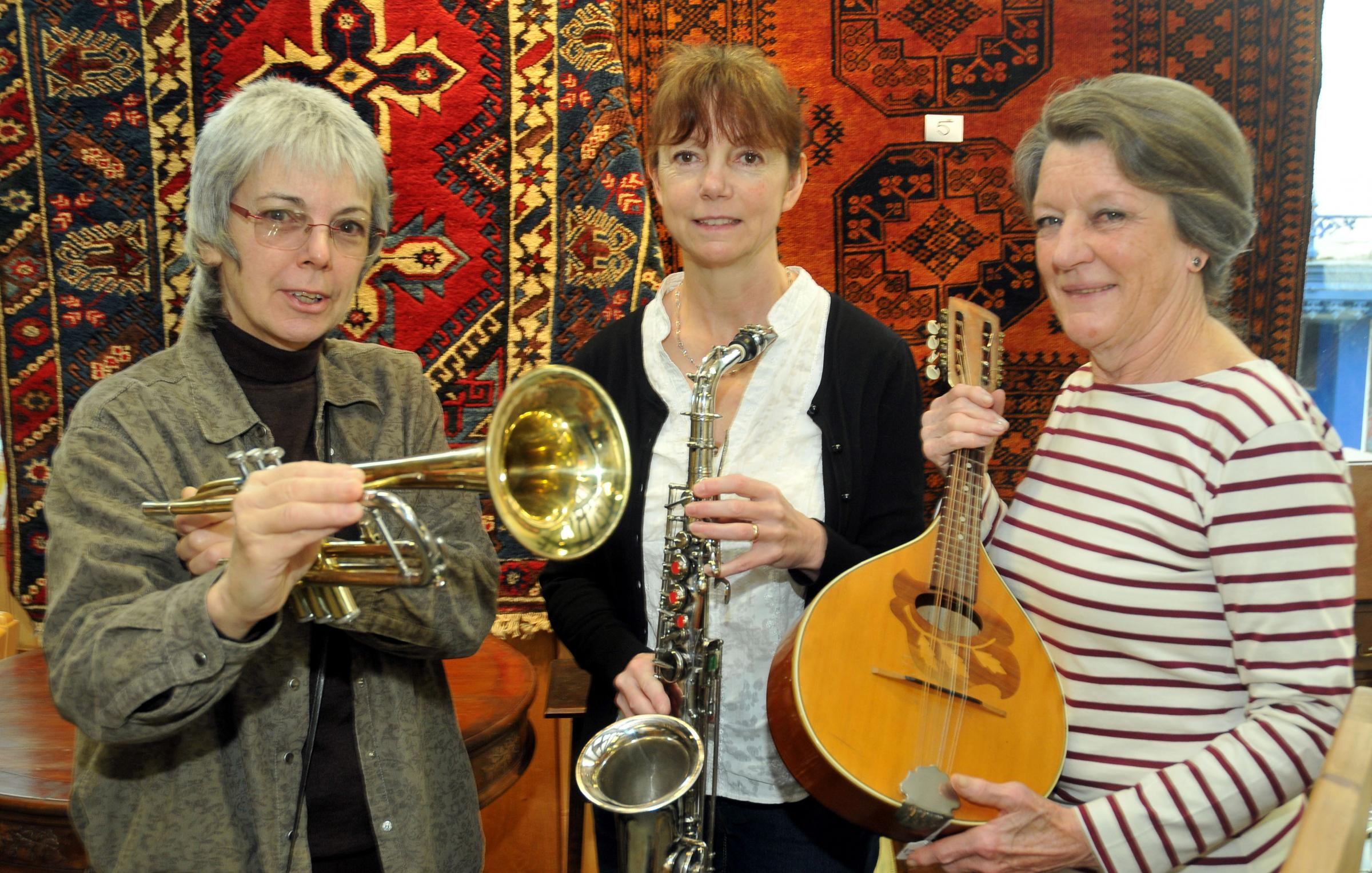 Community auction at Bishops Castle Town hall. With some of the musical items to go under the hammer are from left Town Hall Trustee Evelyn Bowles, one of the town hall managers Julie Magill and volunteer Joan Waters
