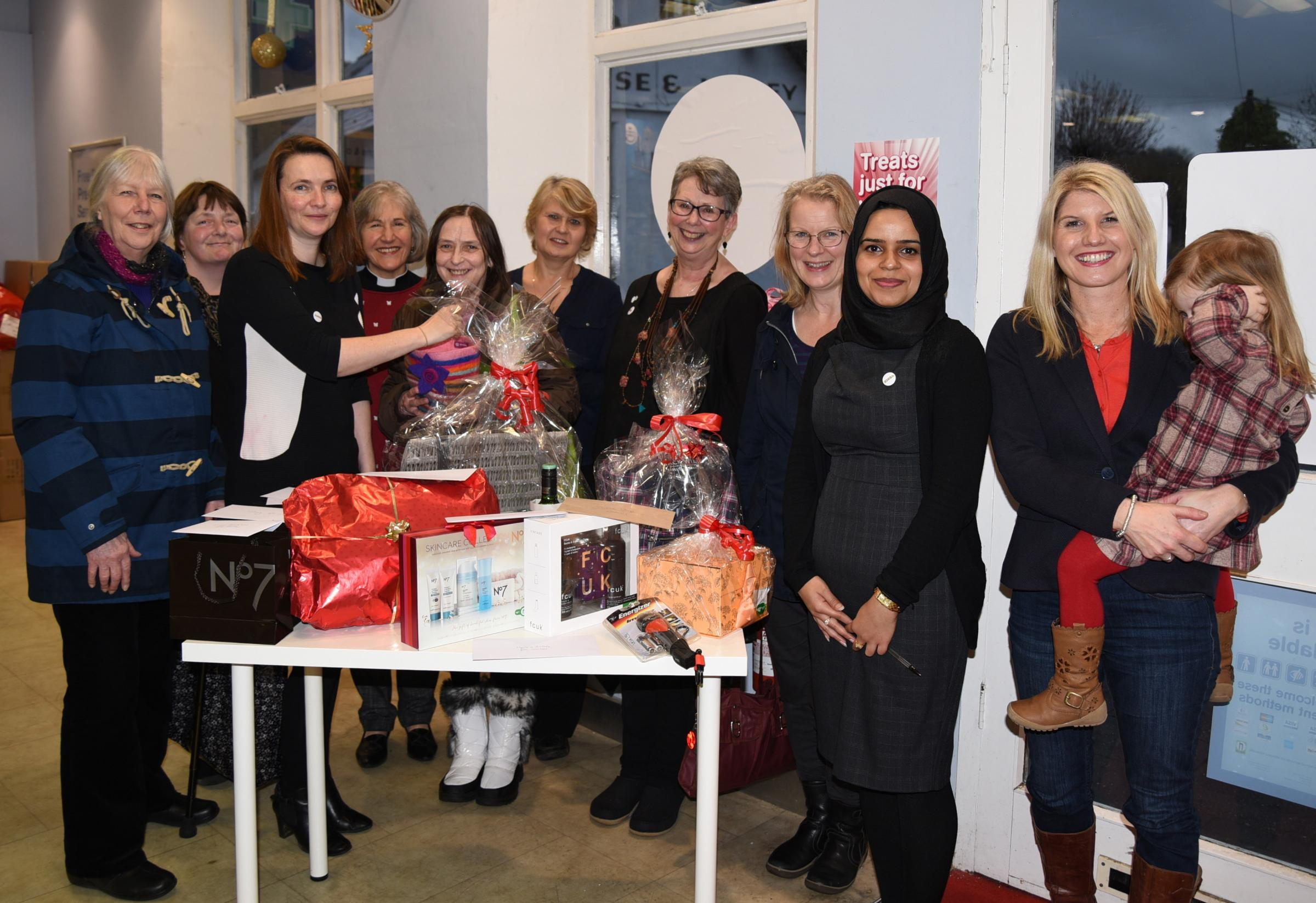 KINDA members Kris Keefe and Harri Smith, A.M. Kirsty Williams, KINDA members Rev Melia Cope, Joanne Phelan, Wendy Aynsleigh, Julia Llewellyn Roberts, Louise Croad, Rafia Jamil store manager at Boots and area manager Donna Kakouris and her daughter Bella
