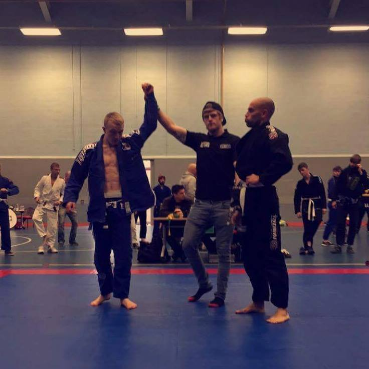 Mitchell Young, with his arm being raised here, has been awarded a Brazilian Jiu Jitsu Blue Belt