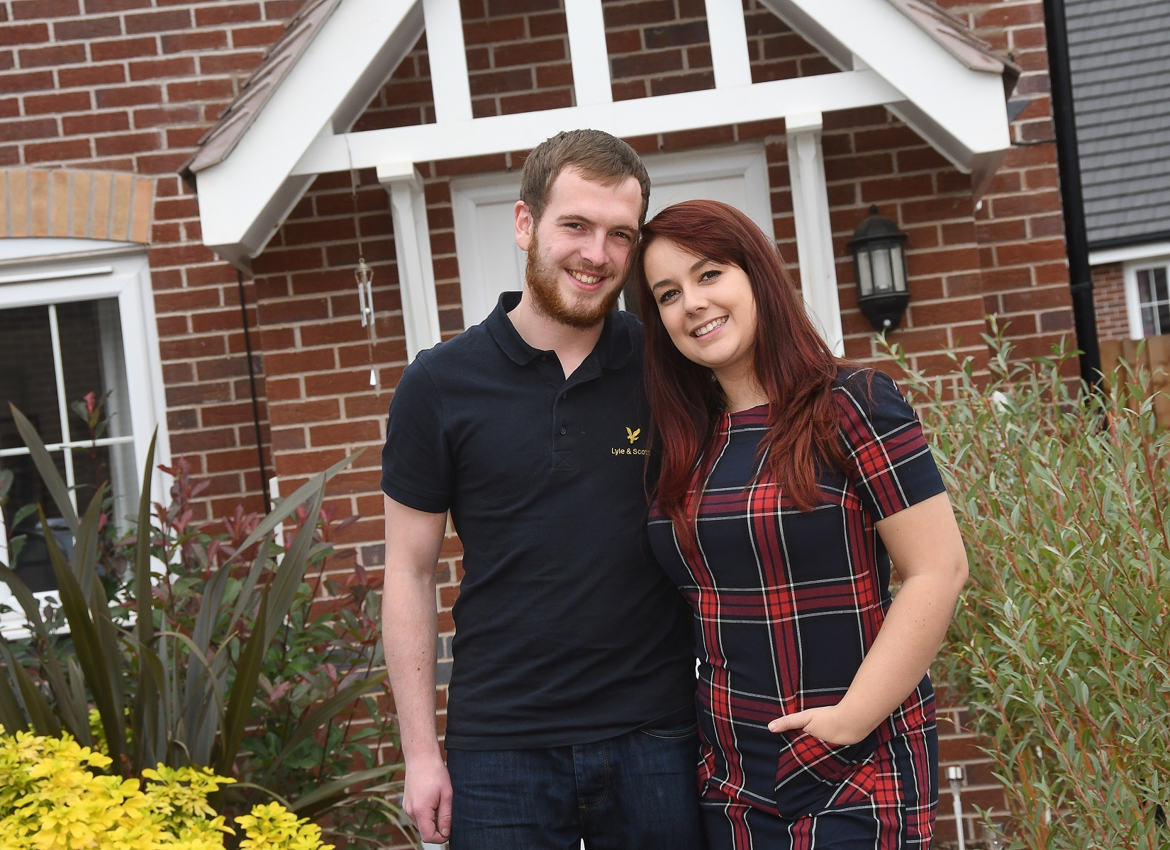 Kieran Chambers and Jade Edwards outside their new two bedroom Newton home style at Bishop Fields