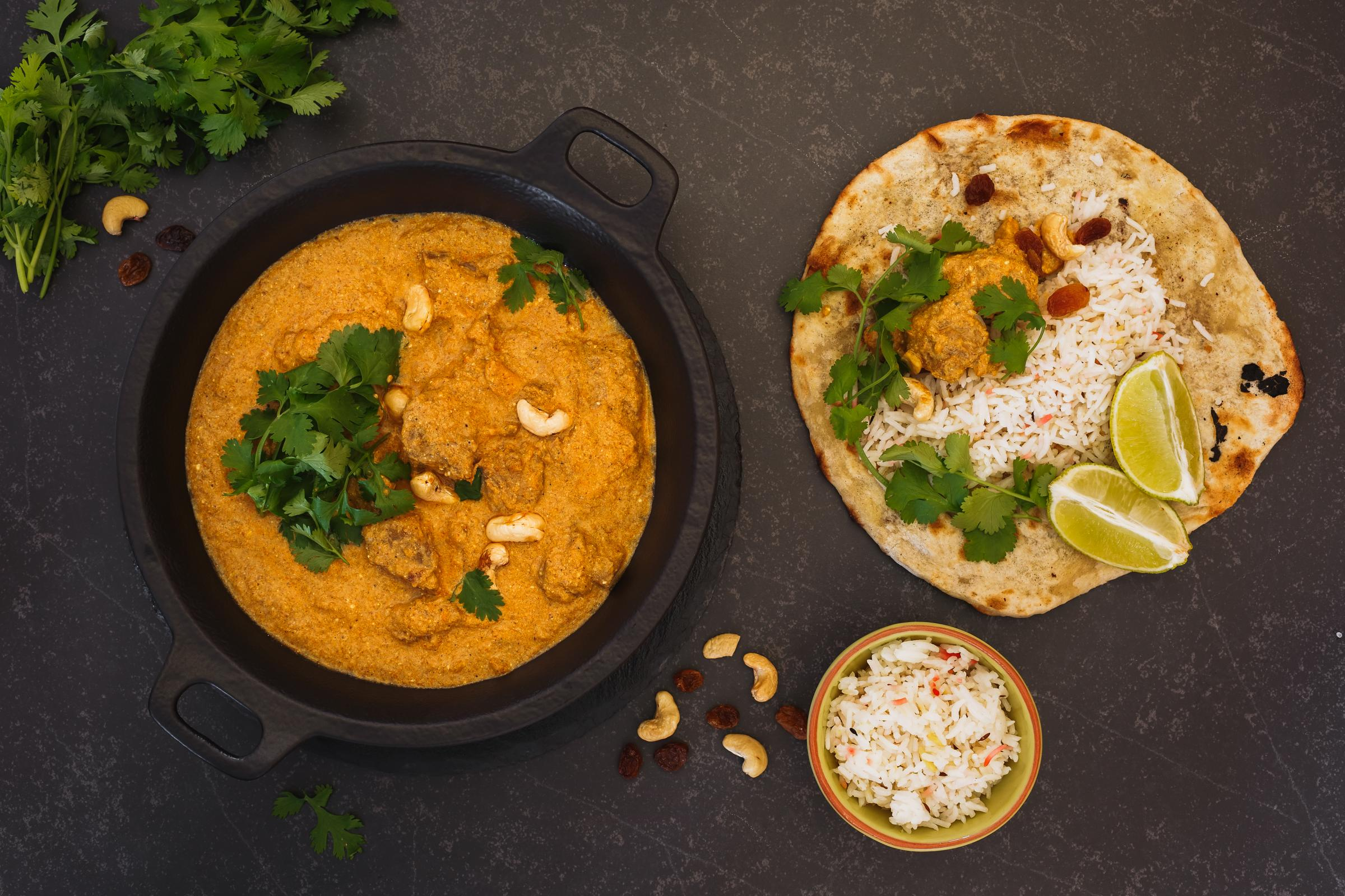 Indian curry meal, lamb korma with cashew nuts, rice and peshwari naan