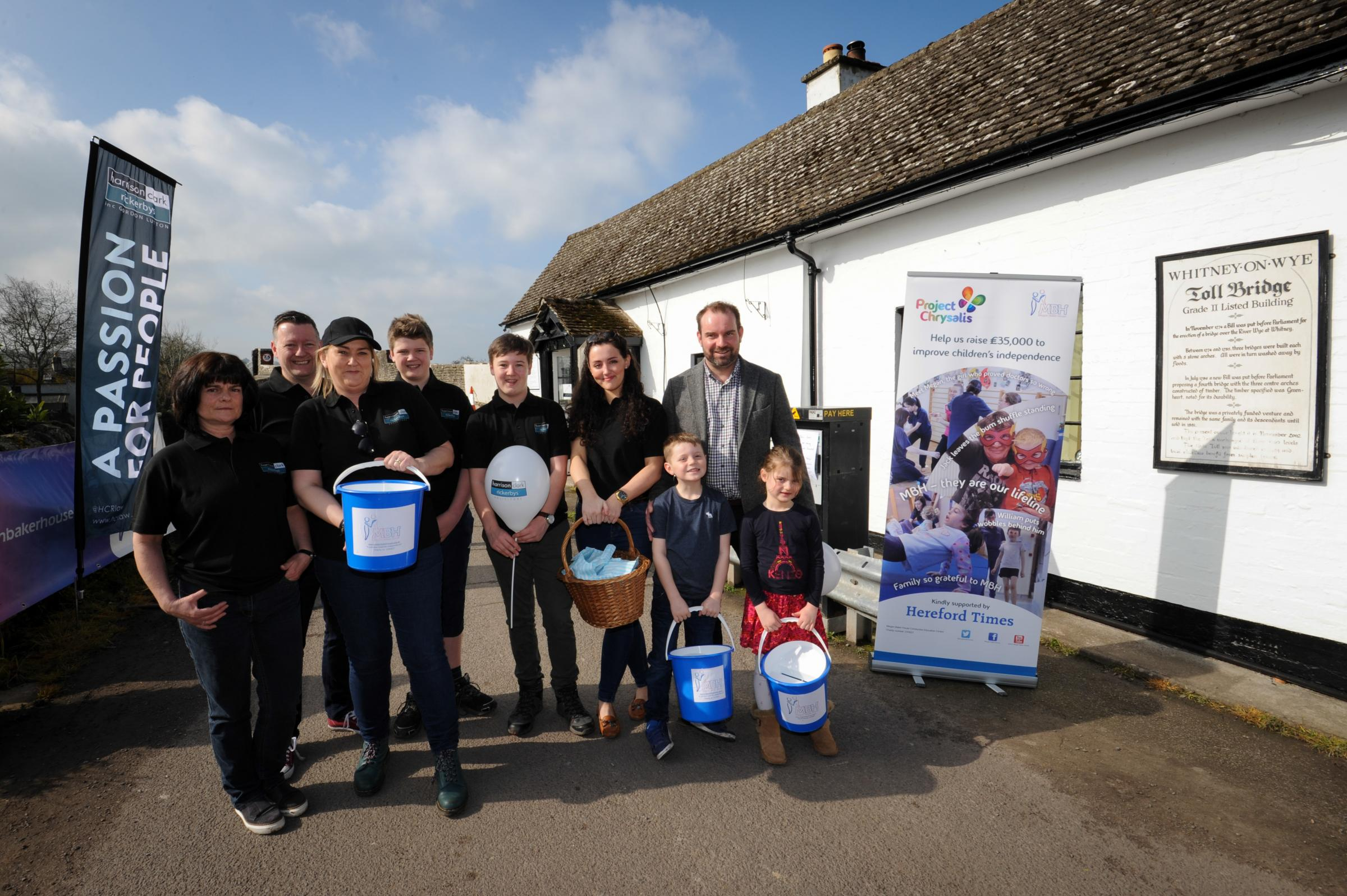 The Harrison Clerk Rickerby team takes control of Whitney on Wye toll bridge for a day to raise money for Megan Baker House. from left: Emma Jennings, Andrew Cooper, Jacob Cooper, William Cooper, Ellis Walby, Hugo Hayes, Matt Hayes, Jemima Hayes.
