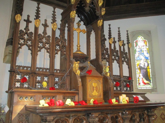 The silk poppies on the altar - red for the soldiers and yellow ones for the munitions makers