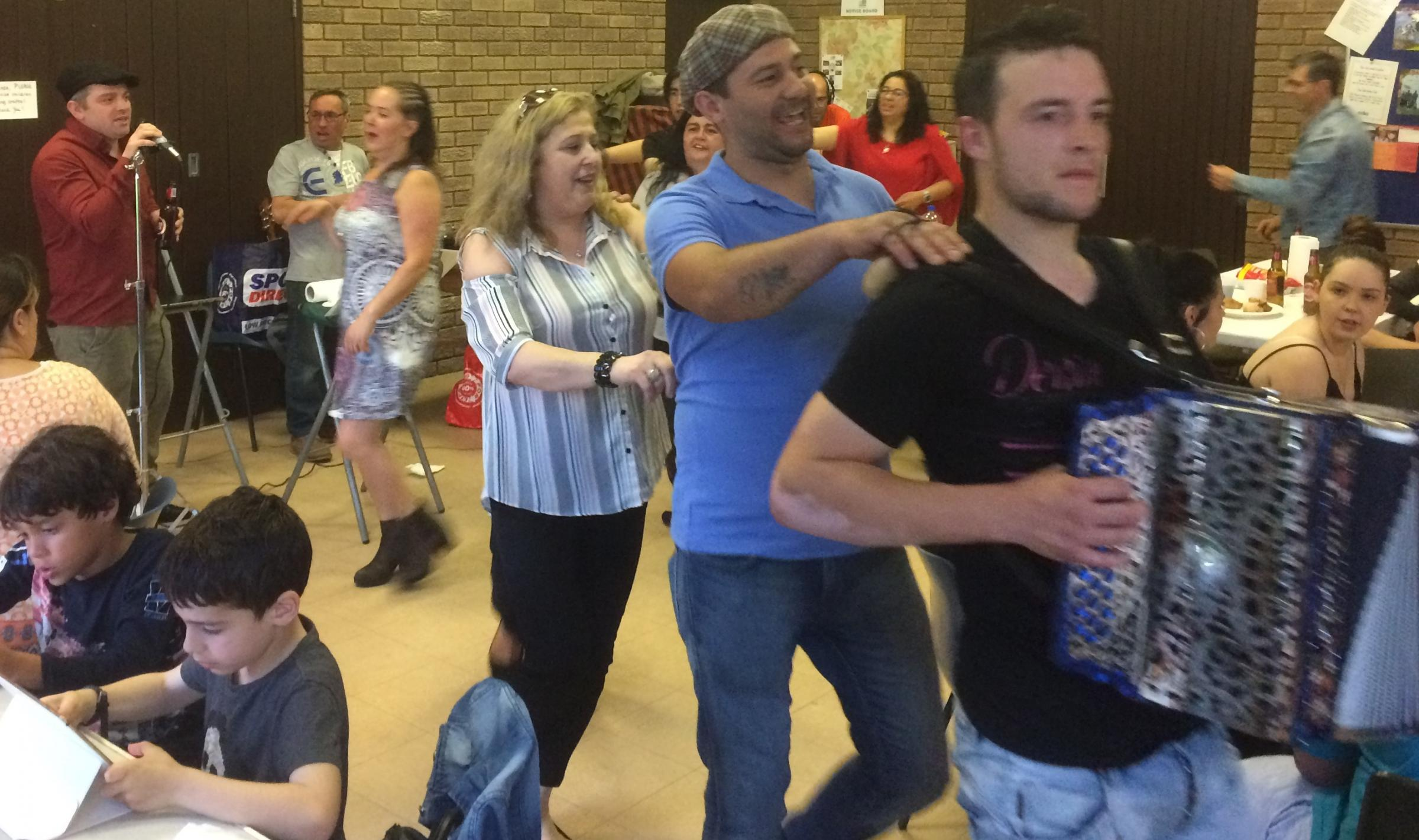Cesario Martinho leads the dance, while playing the accordion, at the party in Hereford