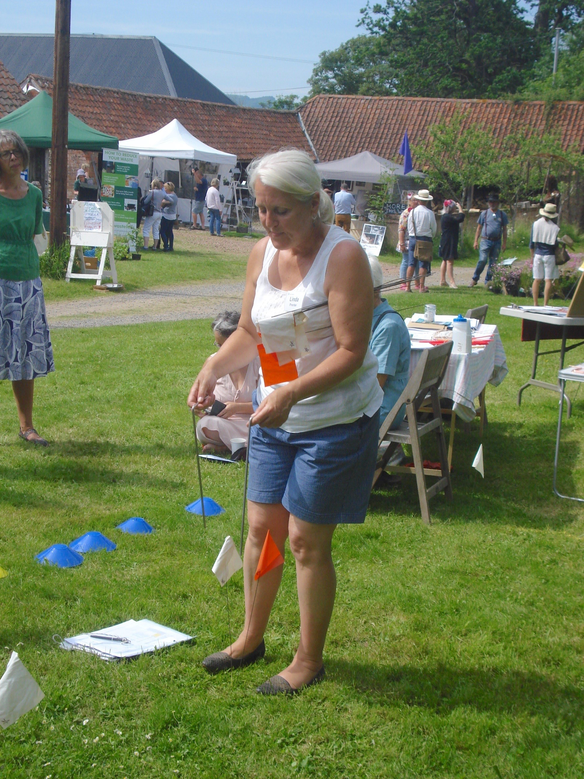 Commercial water dowser, Linda Prenter, demonstrates the use of flags to mark underground water lines at Hellens Garden Festival