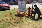 An adopted Leominster soldier next to a display of poppies