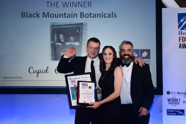 Glyn Bufton and Lloyd Reed from Black Mountain Botanicals collect the award from Jenny Evans of Cupid Events.