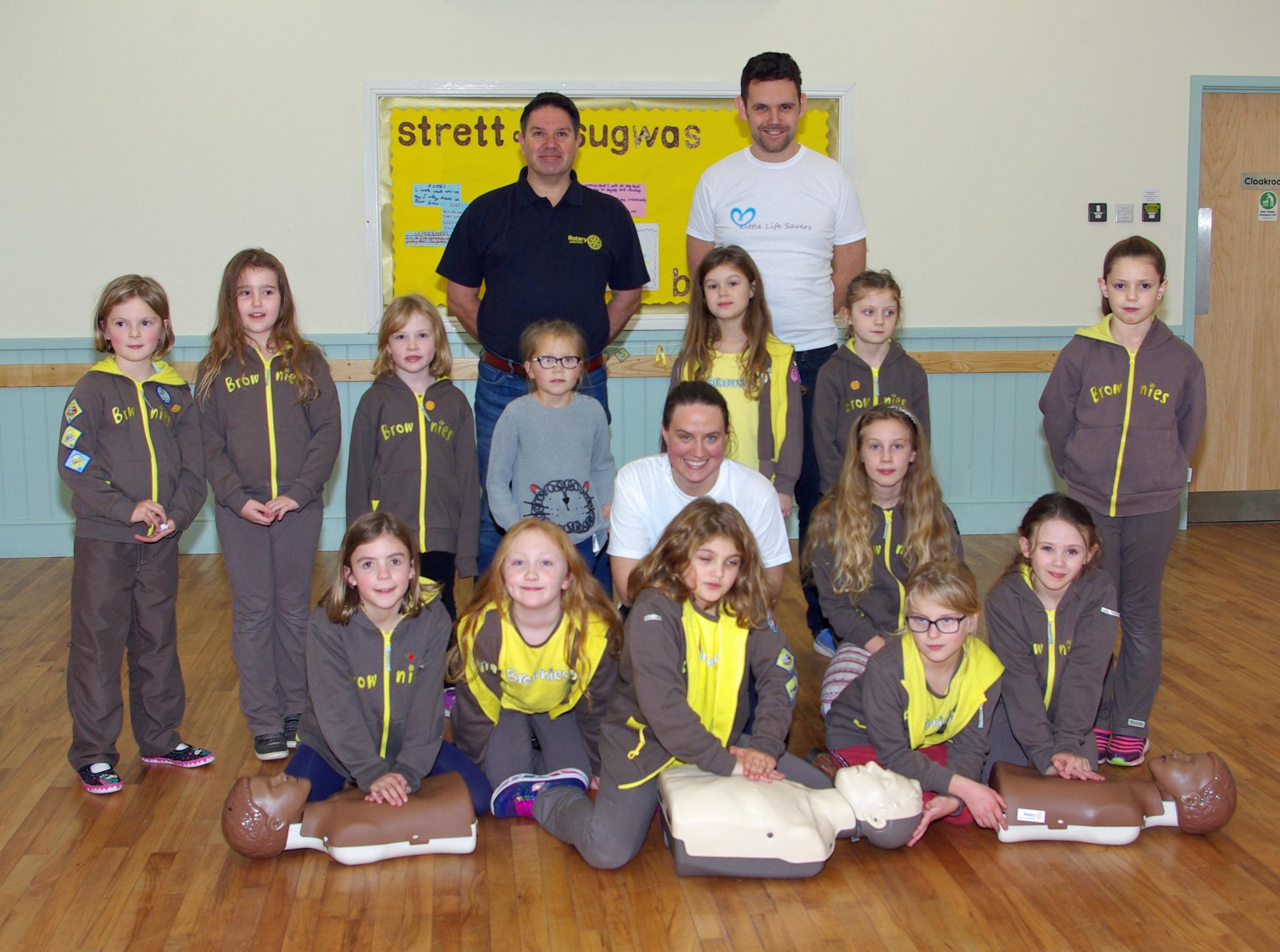Dr Laura Handscombe gives Stretton Sugwas Brownies some lifesaving instruction at the launch of the Little Lifesavers programme at Stretton Sugwas Village Hall, watched by Dr Ryan O'Leary (back right) and City of Hereford Rotary Club's John Taylor