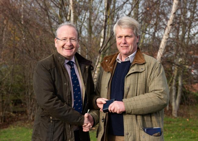 Des Kelly (left) is handed the Hereford Cattle Society's president's badge by outgoing president Jonathan Moorhouse