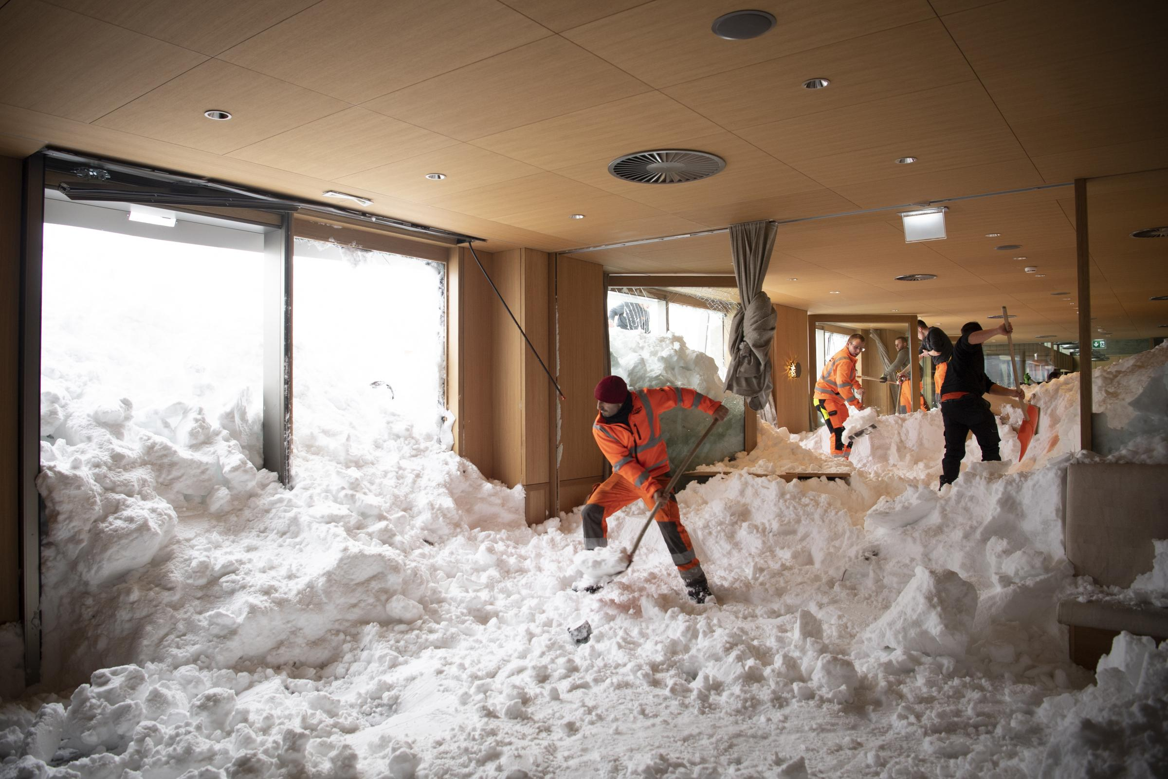 People clear snow from inside the Hotel Saentis in Schwaegalp, Switzerland