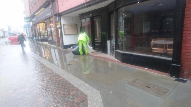 A man in a high-vis jacket removes bedding from the doorway in Commercial Street, Hereford. Photo: Siemon Rice