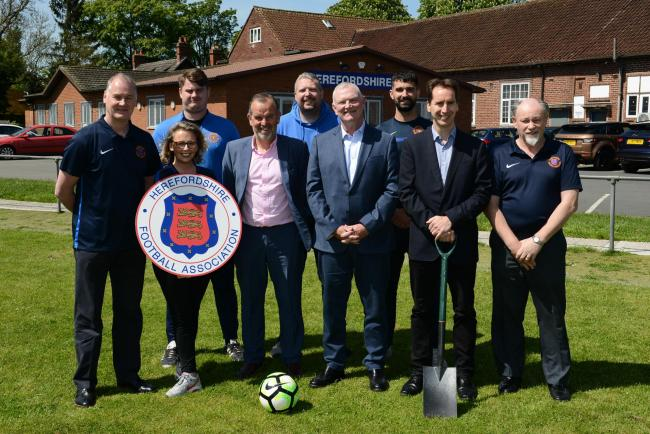 FA chief executive Mark Bullingham (second right) and FA chairman Greg Clarke (fourth from right) with staff from the Herefordshire FA ahead of the installation of a 3G pitch at the County Ground off Widemarsh Common in Hereford. Photo: James Maggs.